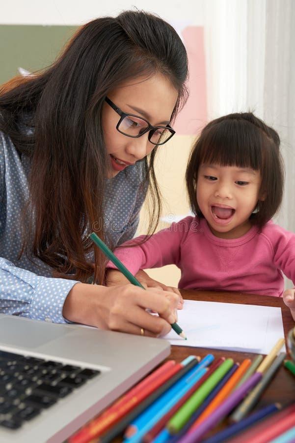 Nettes Mädchen mit der Mutter, die zusammen zeichnet lizenzfreies stockbild