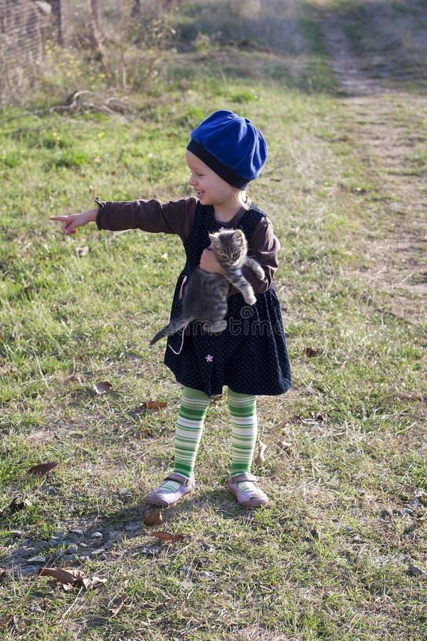 Nettes Mädchen mit einem Kätzchen an Hand zeigt lizenzfreie stockbilder