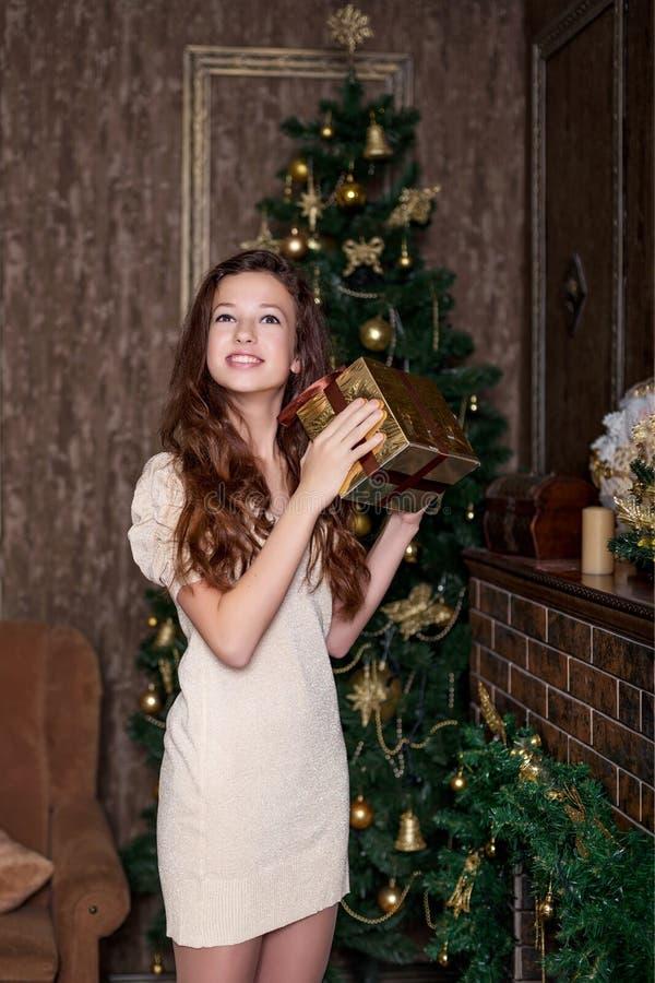 Nettes Mädchen mit einem Weihnachtsgeschenk in den Händen in der glücklichen Stellung der Freude im Wohnzimmer einer klassischen  lizenzfreie stockfotografie