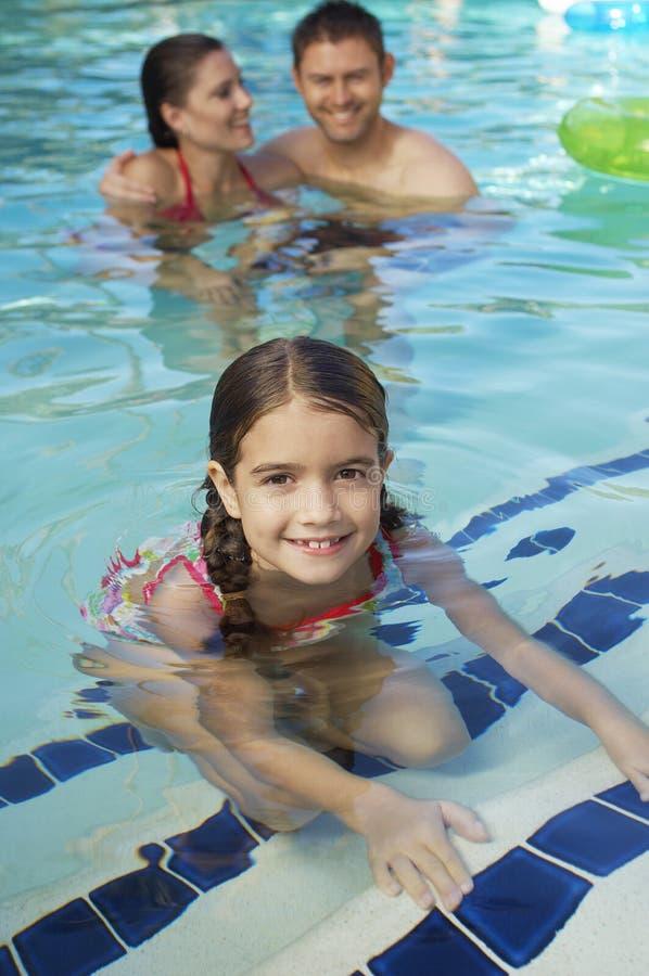 Nettes Mädchen mit Eltern im Pool lizenzfreies stockbild