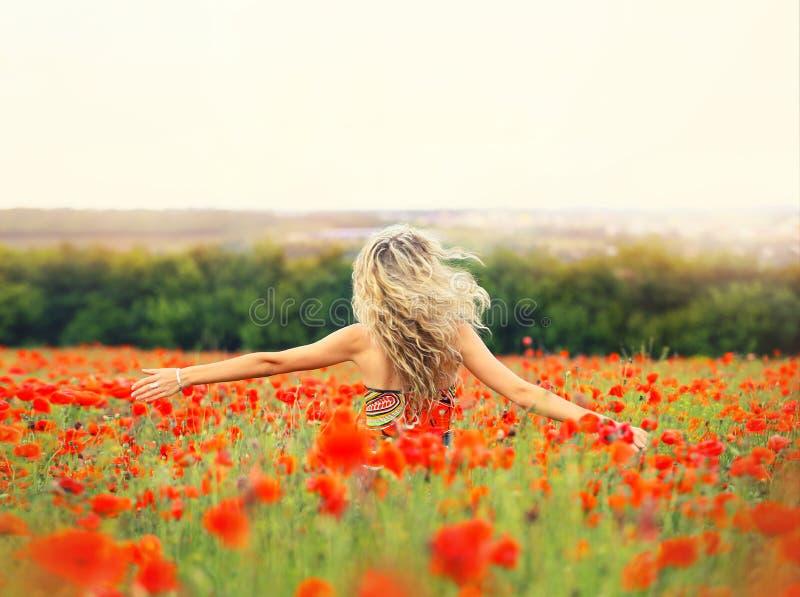 Nettes Mädchen mit gelockten Tänzen des blonden Haares auf einem enormen Mohnblumengebiet allein, ihr Haar fliegt wegen des Windf lizenzfreie stockfotografie