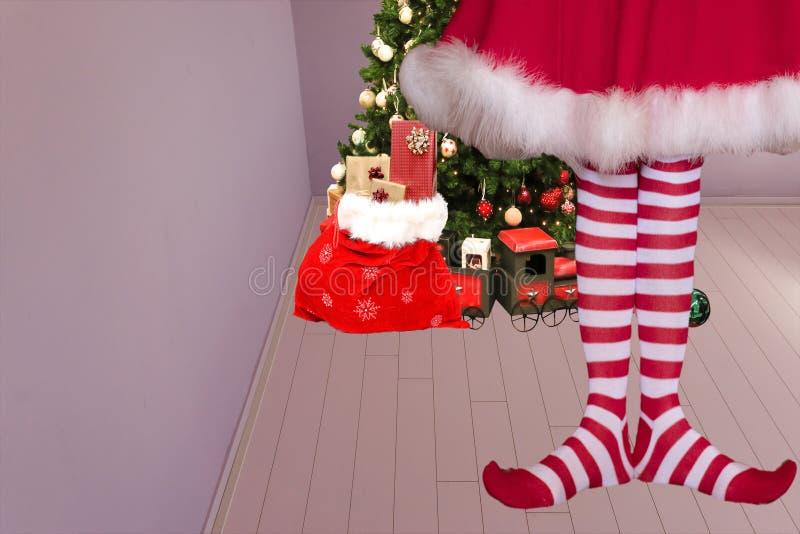 Nettes Mädchen mit gezeigt, die Füße legging Stellung der Elfe in einem Raum mit einem Weihnachtsbaum und in Weihnachtsmann-Tasch lizenzfreies stockfoto