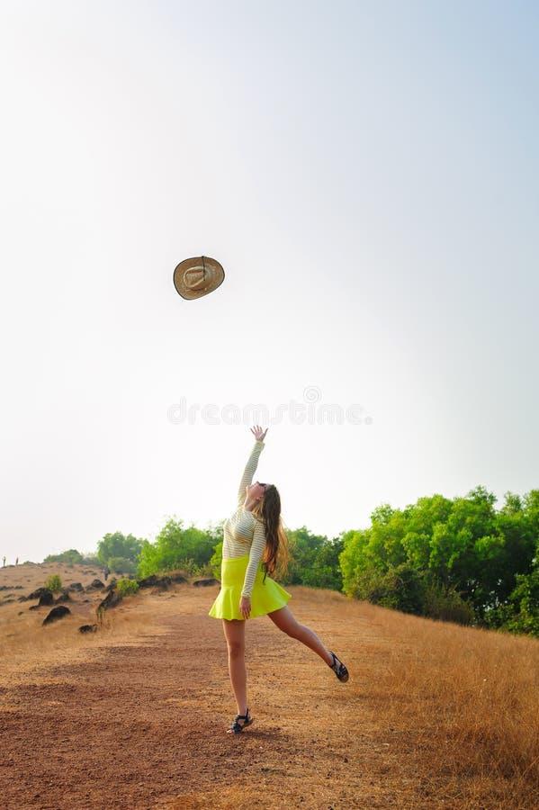 Nettes Mädchen mit langem Haarsprungs- und -Wurfsstrohhut in der Luft Junge brunette Frau in den Wegen des kurzen Rockes auf Hüge lizenzfreie stockfotografie