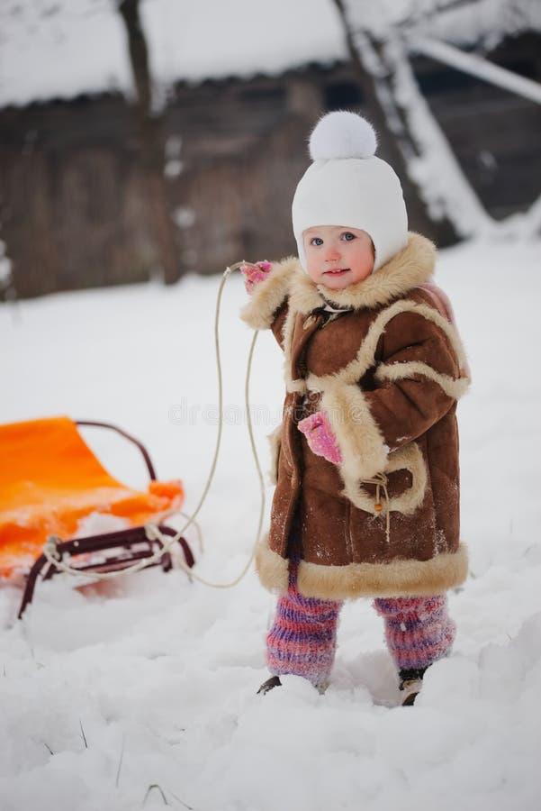 Nettes Mädchen mit Schlitten im Schnee stockbild