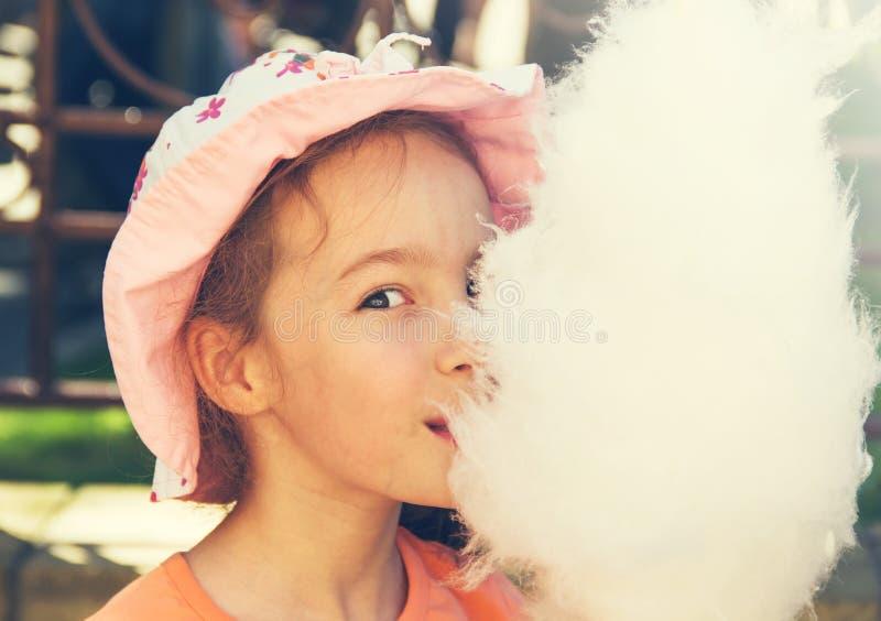 Nettes Mädchen mit weißer Zuckerwatte getont stockfoto
