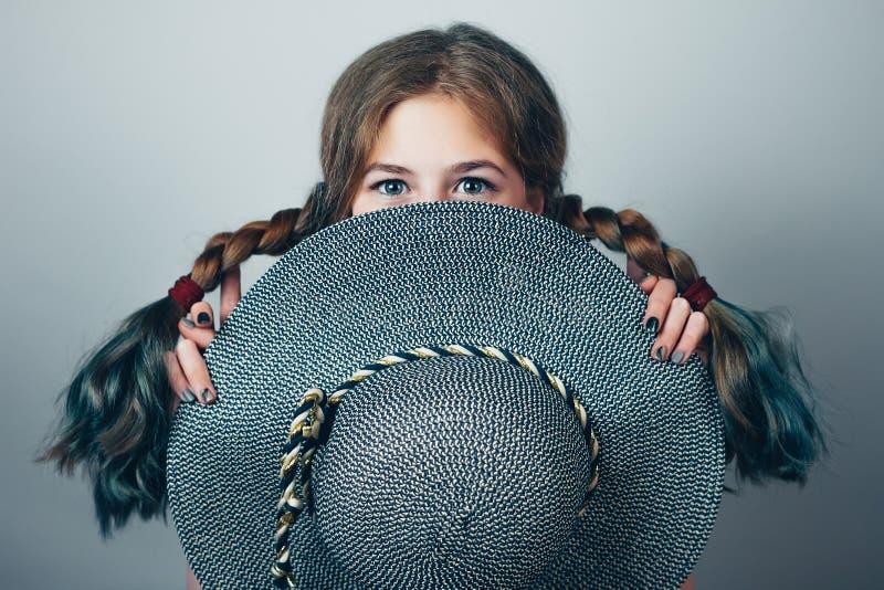 Nettes Mädchen mit Zöpfen bedeckt ihr Gesicht mit einem runden Hut lizenzfreies stockfoto