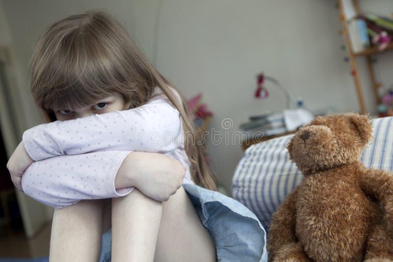 Nettes Mädchen sieben Jahre alte Sitzen auf Bett und cryi lizenzfreies stockfoto
