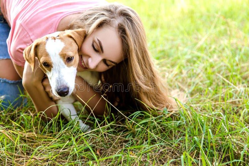 Nettes Mädchen spielt mit ihrem Hund im Park lizenzfreies stockfoto