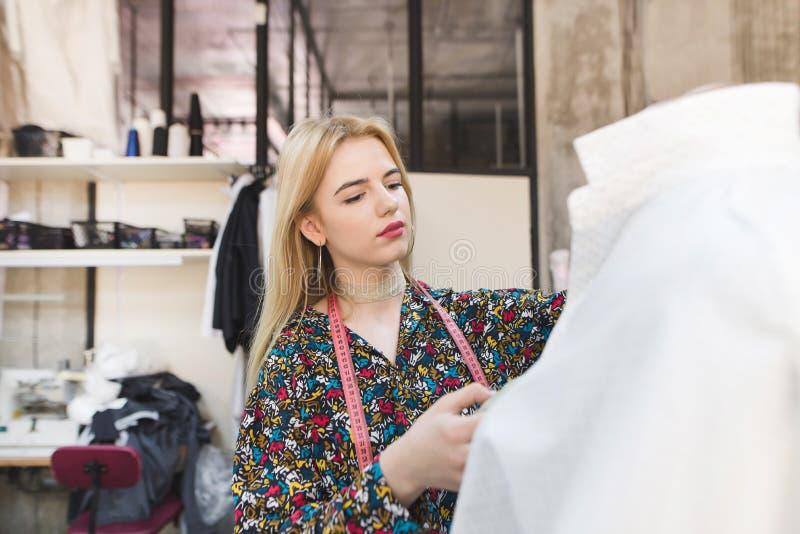 Nettes Mädchen steht die Attrappe mit Kleidung und dem Arbeiten bereit Schaffung von Modekleidung stockfotos