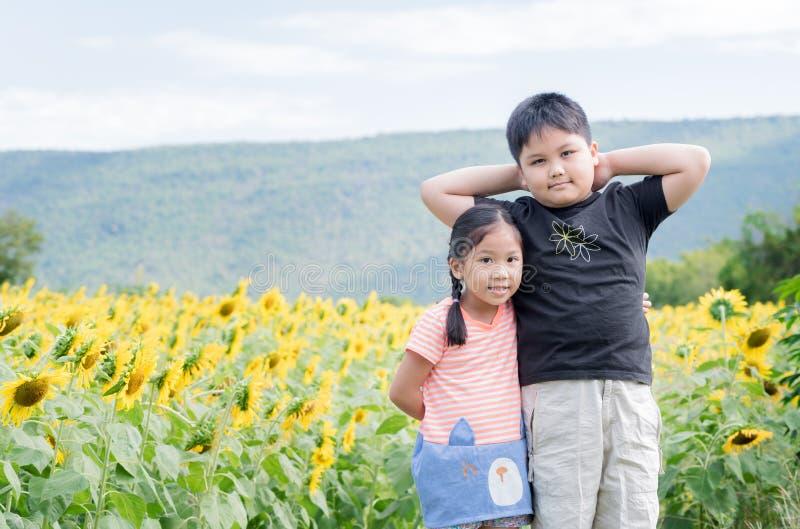 Nettes Mädchen und Junge, die Spaß im Sonnenblumenfeld umarmt lizenzfreie stockbilder