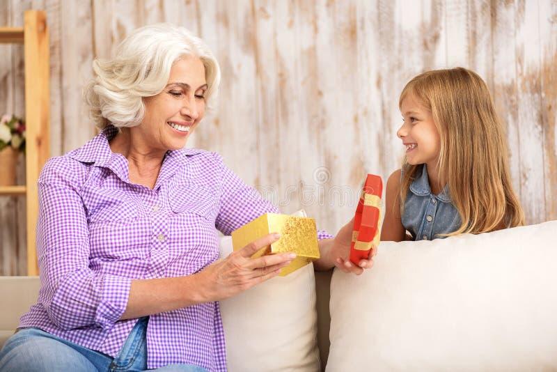 Nettes Mädchengeben ihrer Großmutter vorhanden stockfotografie