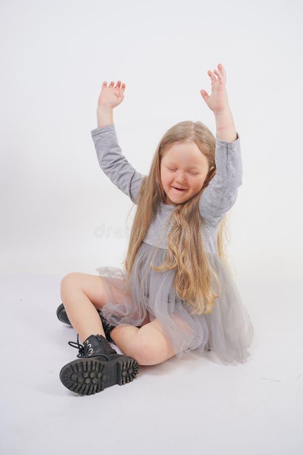 Nettes Mädchenkind mit dem langen blonden Haar, das süß auf dem Boden und dem Gegähne, ihre Hände in den verschiedenen Richt stockbild