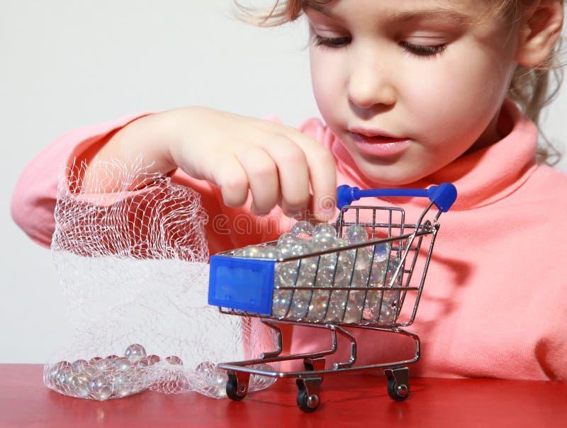 Nettes Mädchensorgfaltspiel mit Spielzeugeinkaufenlaufkatze stockbild