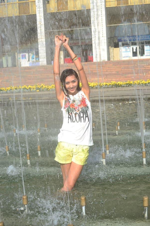 Nettes Mädchentanzen unter Wasserstrahlen im Stadtbrunnen lizenzfreies stockbild