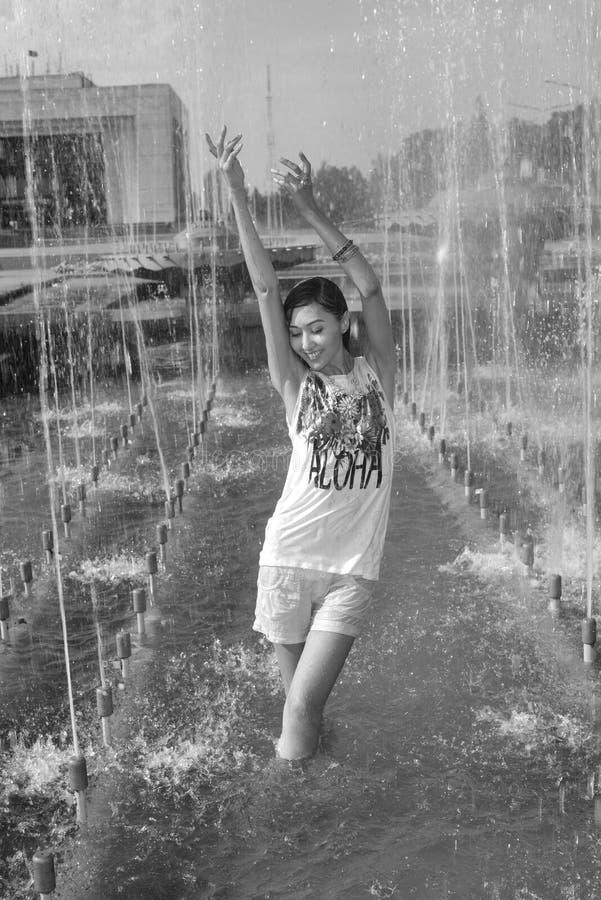 Nettes Mädchentanzen unter Wasserstrahlen im Stadtbrunnen stockbild