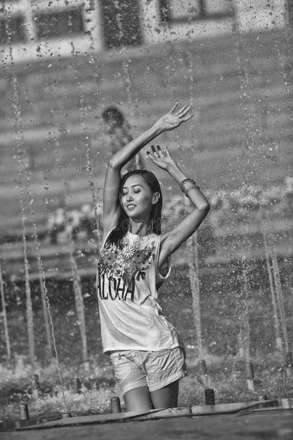 Nettes Mädchentanzen unter Wasserstrahlen im Stadtbrunnen lizenzfreie stockfotografie
