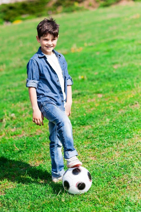 Nettes männliches Kind tut Sporttätigkeit stockfotografie