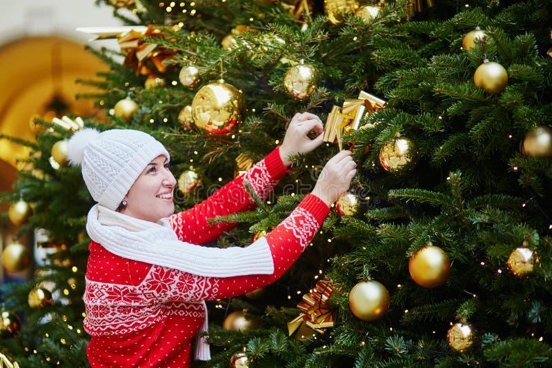 Nettes M?dchen in der roten Winterstrickjacke nahe Weihnachtsbaum lizenzfreie stockfotografie