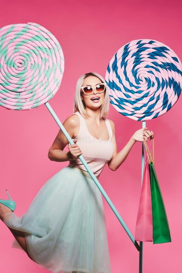 Nettes Modell mit Bonbons und Einkaufstaschen stockfotografie
