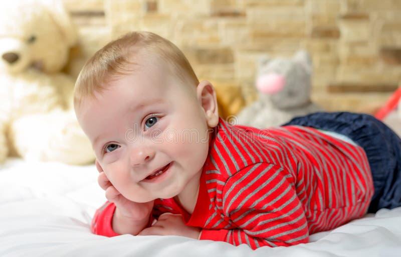 Nettes molliges kleines Baby mit einem glücklichen Lächeln stockfoto