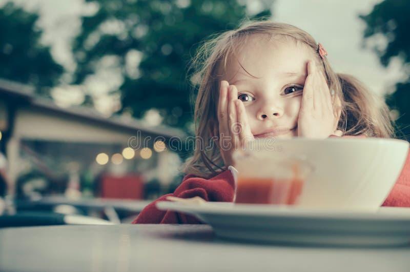 Nettes nachdenkliches kleines Mädchen mit Ellbögen auf dem Tisch stockfotos