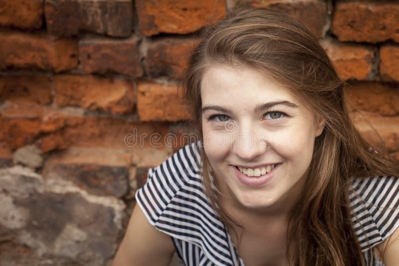 Nettes Nahaufnahmeporträt des jungen Mädchens nahe einer Backsteinmauer glück stockfotografie