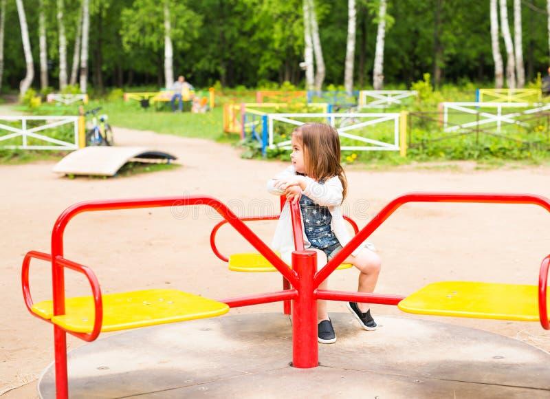 Nettes nettes kleines Mädchen fährt auf Karussell stockfotografie
