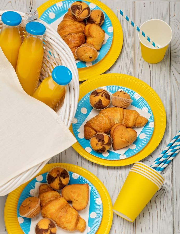 Nettes neues Lebensmittel und Korb auf dem Gras Süßes Picknick - Orangensaft und Muffins, croissan stockfotos