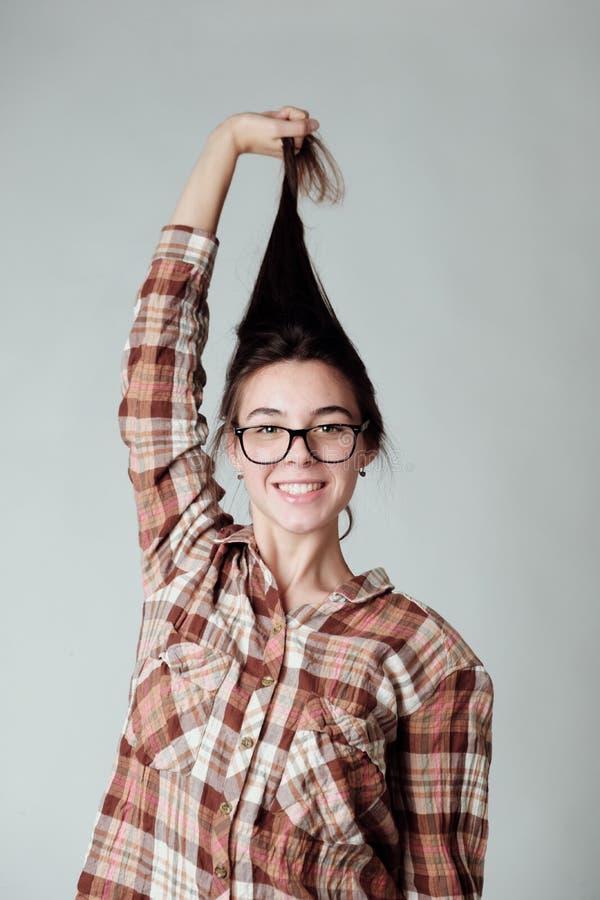 Nettes nurd brunette Mädchen im Holzfällerkarohemd, das mit dem Haar spielt lizenzfreies stockbild
