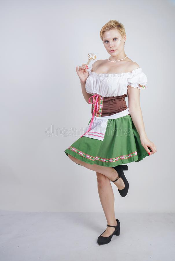 Nettes Plusgrößenmädchen mit einem kurzen Haarschnitt und großen Brüsten gekleidet in einem nationalen bayerischen Kleid auf eine stockbild