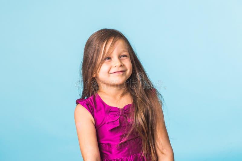 Nettes nettes Porträt des kleinen Mädchens, lokalisiert auf blauem Hintergrund lizenzfreie stockfotos