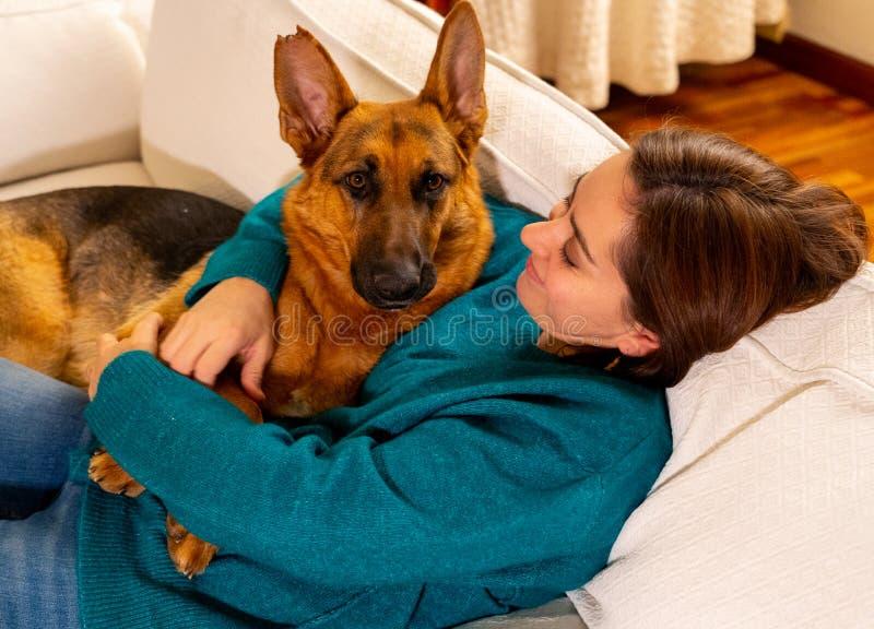 Nettes Porträt des Schäferhunds der jungen Frau und des Hundes, der am gemütlichen Haus im Winter umarmt lizenzfreie stockfotos