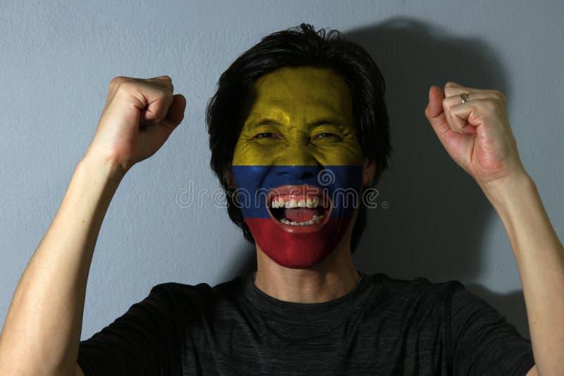 Nettes Porträt eines Mannes mit der Flagge des Kolumbiens malte auf seinem Gesicht auf grauem Hintergrund stockbild