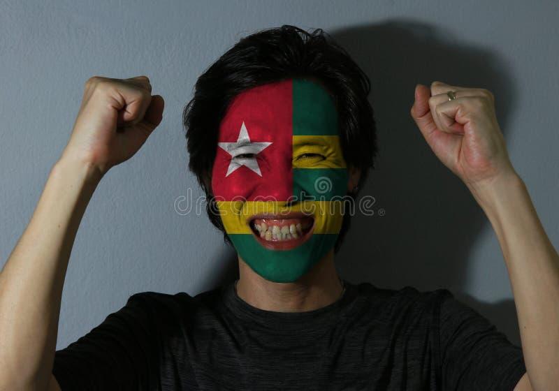 Nettes Porträt eines Mannes mit der Flagge von Togo malte auf seinem Gesicht auf grauem Hintergrund Das Konzept des Sports oder d lizenzfreie stockfotos
