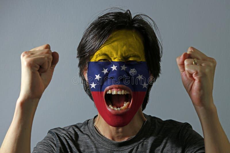 Nettes Porträt eines Mannes mit der Flagge von Venezuela malte auf seinem Gesicht auf grauem Hintergrund Das Konzept des Sports o lizenzfreies stockfoto