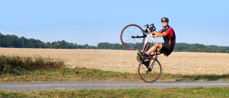 Nettes Radfahrerreiten auf dem Hinterrad stockfoto