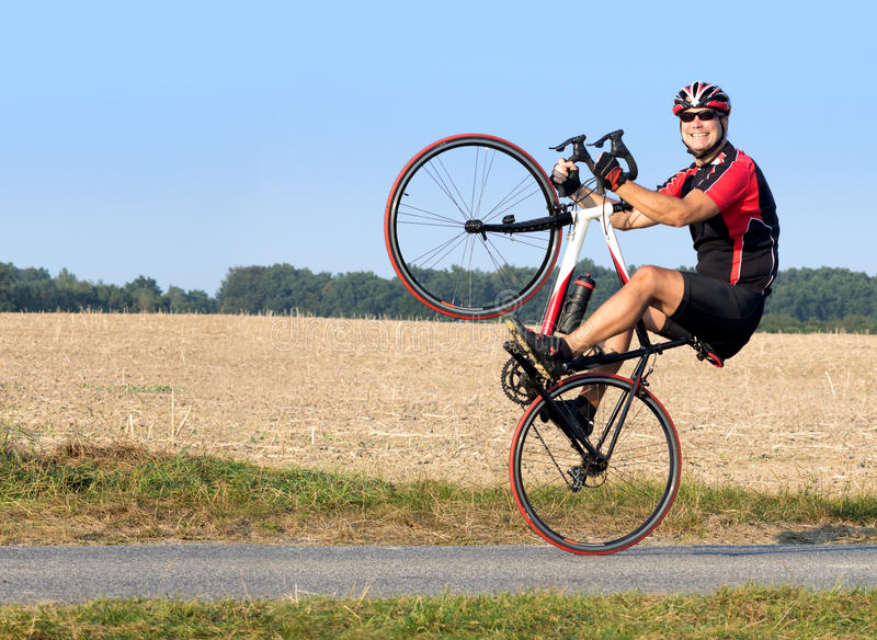 Nettes Radfahrerreiten auf dem Hinterrad lizenzfreie stockfotos