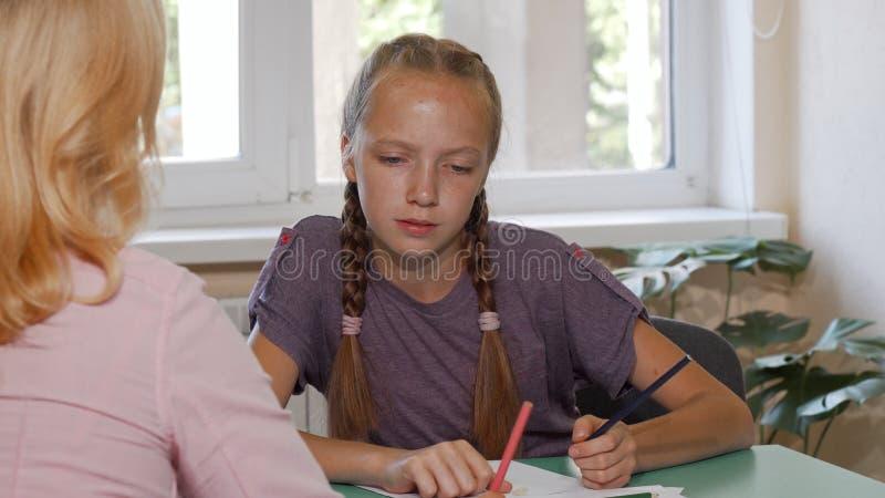 Nettes rotes behaartes Schulmädchen, das an ihrem Kunstprojekt mithilfe des Lehrers arbeitet lizenzfreies stockbild