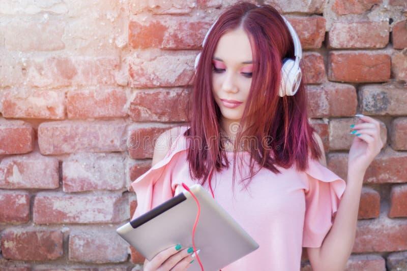 Nettes Rothaarigemädchen, das Musik auf digitaler Tablette mit Kopfhörern gegen die Backsteinmauer im Freien hört stockfotos