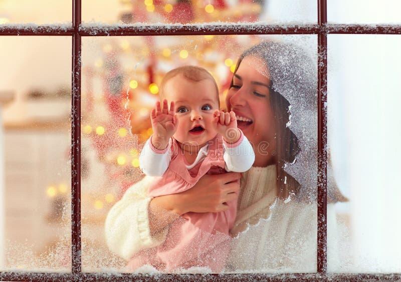Nettes Säuglingsbaby in der Mutterhand, die durch das Fenster, Familienwinterurlaube schaut lizenzfreies stockbild