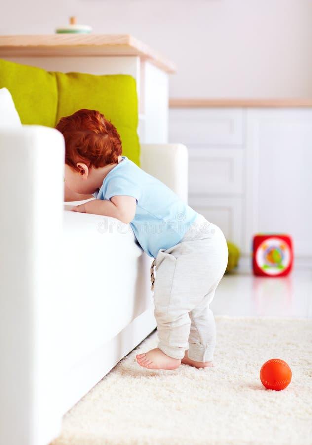 Nettes Säuglingsingwerbaby, das versucht, die Couch zu Hause zu klettern stockbild
