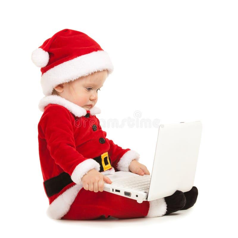 Nettes Sankt-Baby auf dem wei?en Hintergrund Kleines Modell in Sankt-Hut am Studio, das wei?en Laptop h?lt r lizenzfreie stockfotos