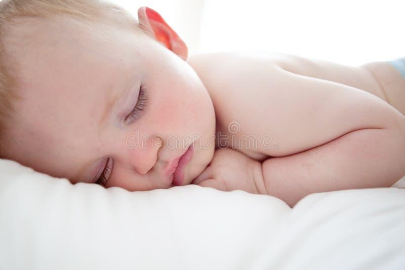 Nettes Schätzchen, das auf seinem Bauch schläft lizenzfreie stockfotografie