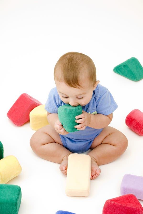 Nettes Schätzchen, das auf Spielzeug kaut lizenzfreies stockbild