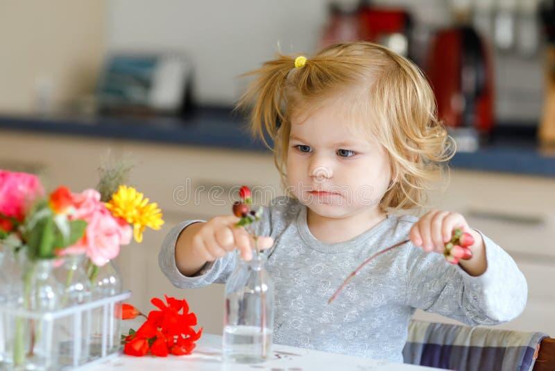 Nettes schönes kleines Kleinkindmädchen, das Blumenblumenstrauß macht Entzückendes Babykind, das mit verschiedenen Blumen spielt  lizenzfreie stockfotografie