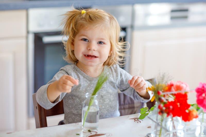 Nettes schönes kleines Kleinkindmädchen, das Blumenblumenstrauß macht Entzückendes Babykind, das mit verschiedenen Blumen spielt  lizenzfreies stockbild