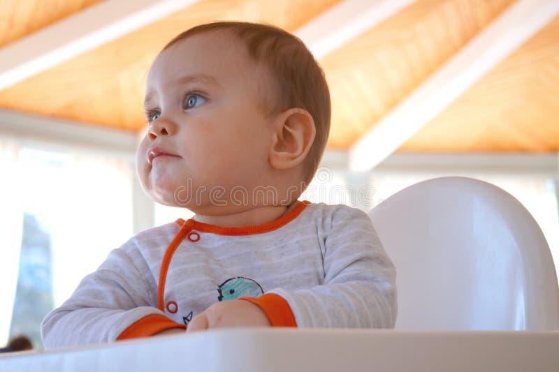 Nettes schönes pralles Baby denkt an etwas lizenzfreie stockfotos
