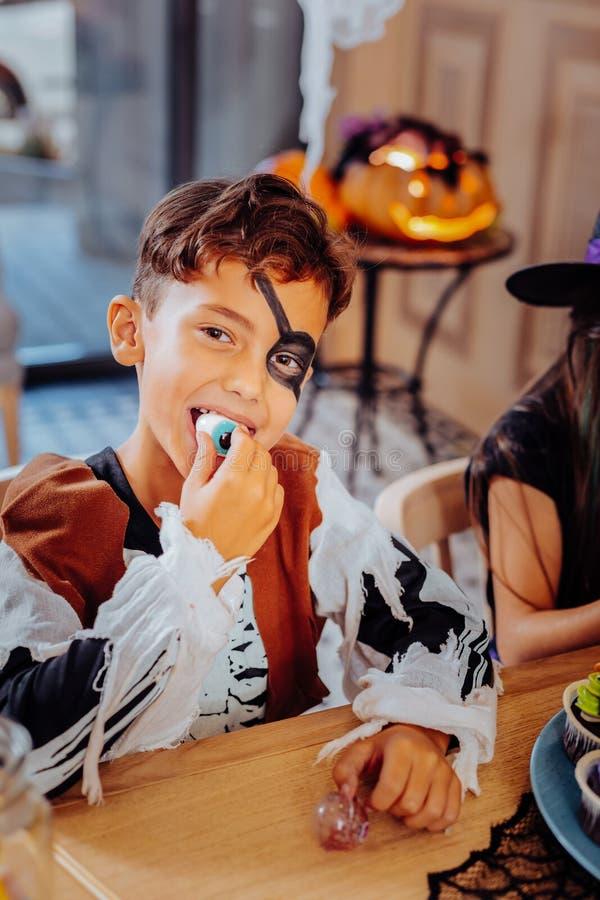 Nettes Schülergefühl beim Essen von gummiartigen Bonbons für Halloween unterhalten lizenzfreies stockfoto