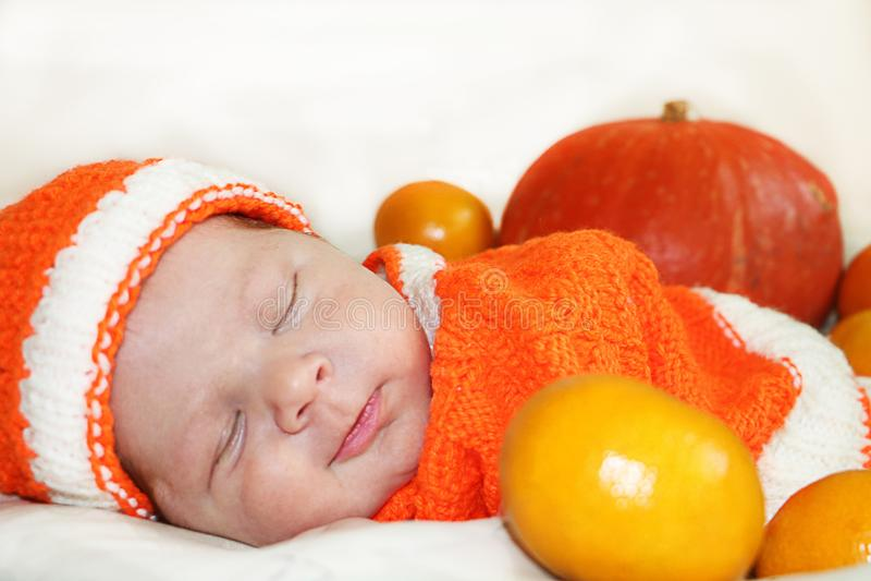 Nettes schlafendes lächelndes neugeborenes Baby kleidete in einer gestrickten Orange an stockfotos