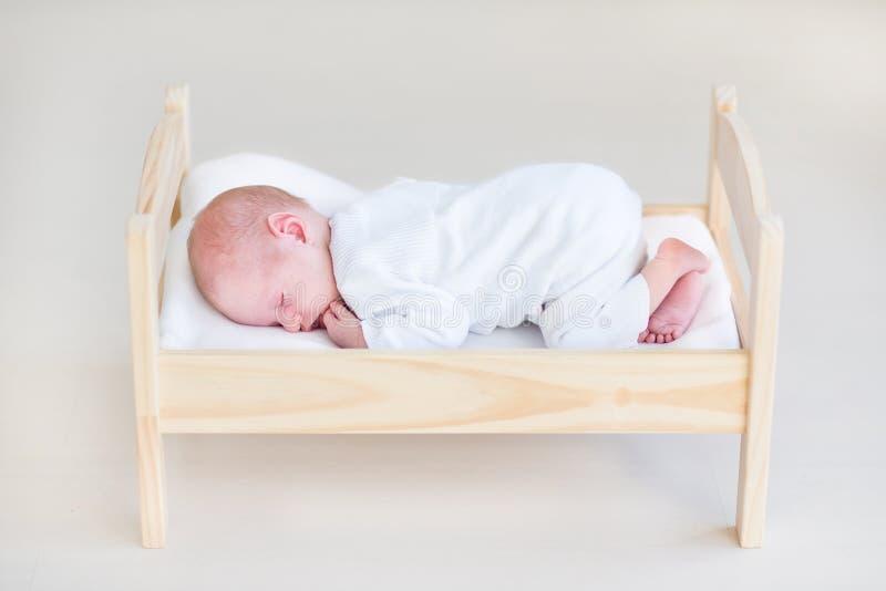Nettes schlafendes neugeborenes Baby in einem Spielzeugbett stockbilder